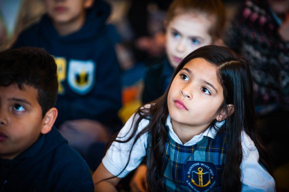 An elementary school scholar listening in class