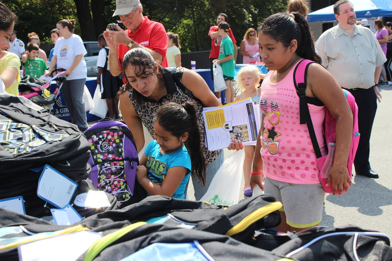 Children receiving backpacks at an event