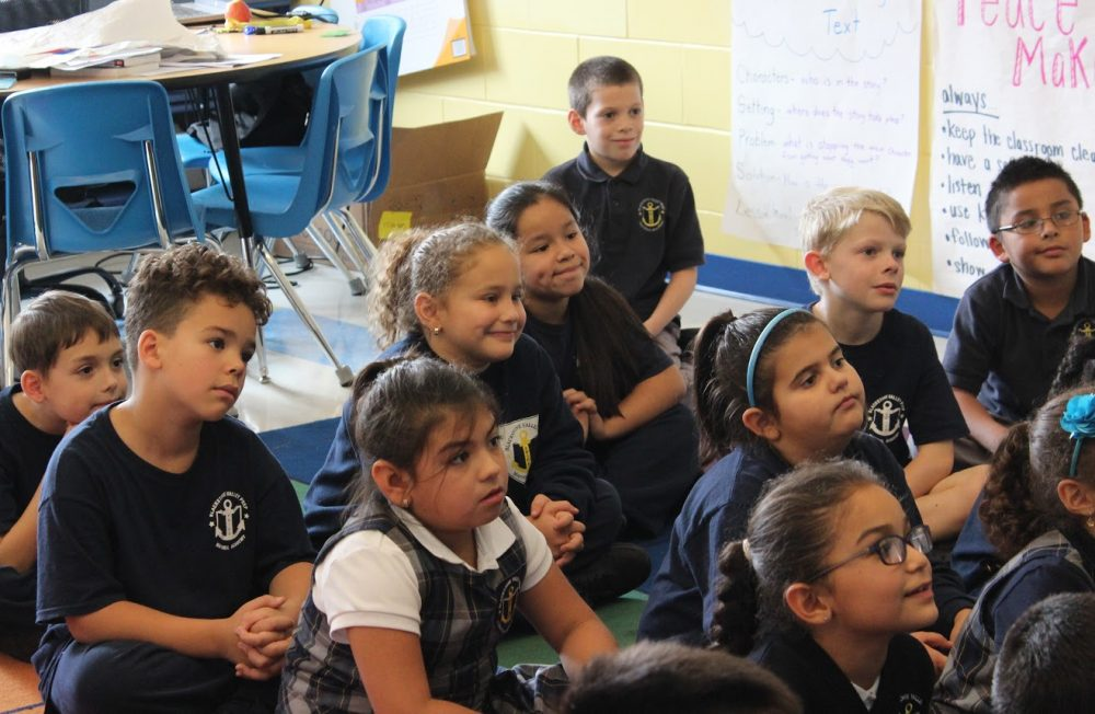 A group of elementary students listening attentively in class