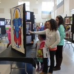 A family observing an art display at the BVP Art Show
