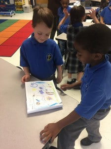 Two male elementary school scholars looking at a scholar-made illustration