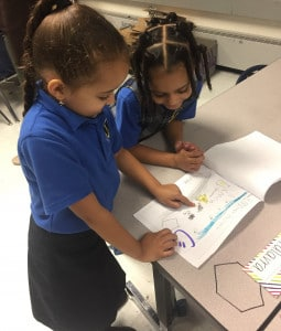 Two female elementary school scholars looking at a scholar-produced drawing