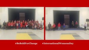 A posed group photo, many of the individuals wearing red for International Women's Day
