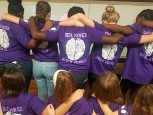 "Girls at Coding Camp huddle up, showing backs of t-shirts that read ""Girl Power, Brain Power"""