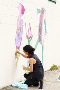 Keri King working on a mural