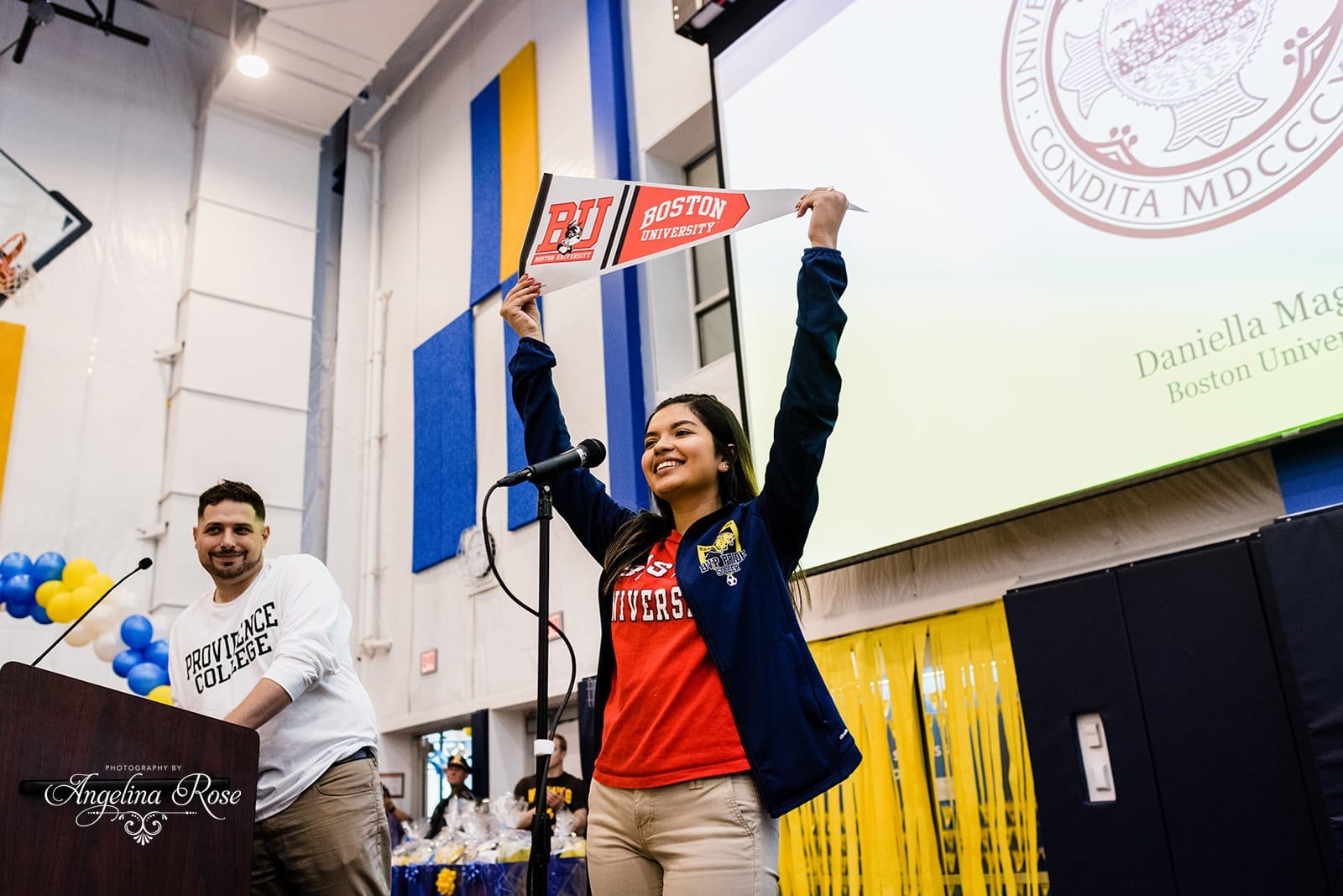 Scholar holding up Boston University pennant