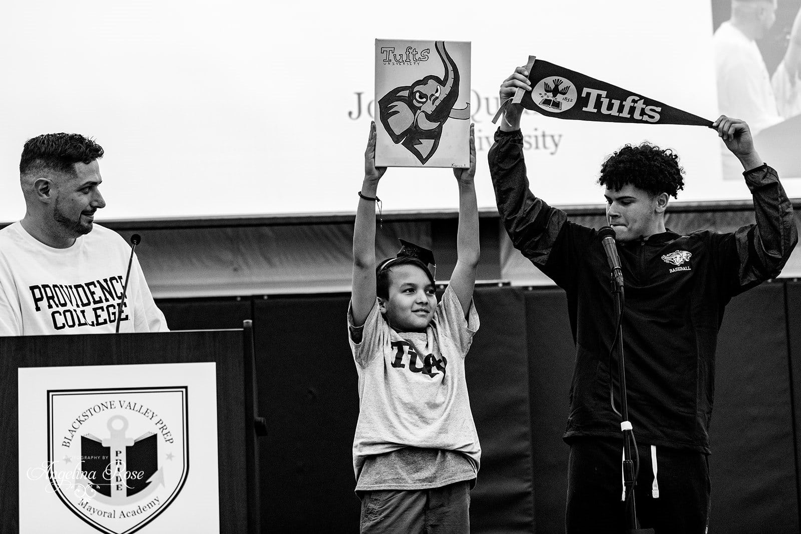 Scholar holding up Tufts pennant with little brother.