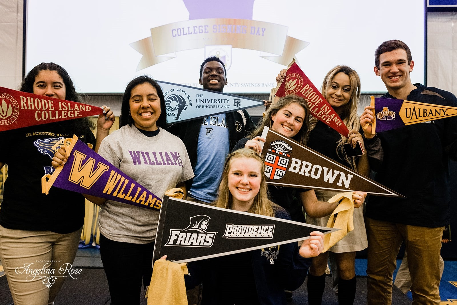 Group of scholars holding up college pennants