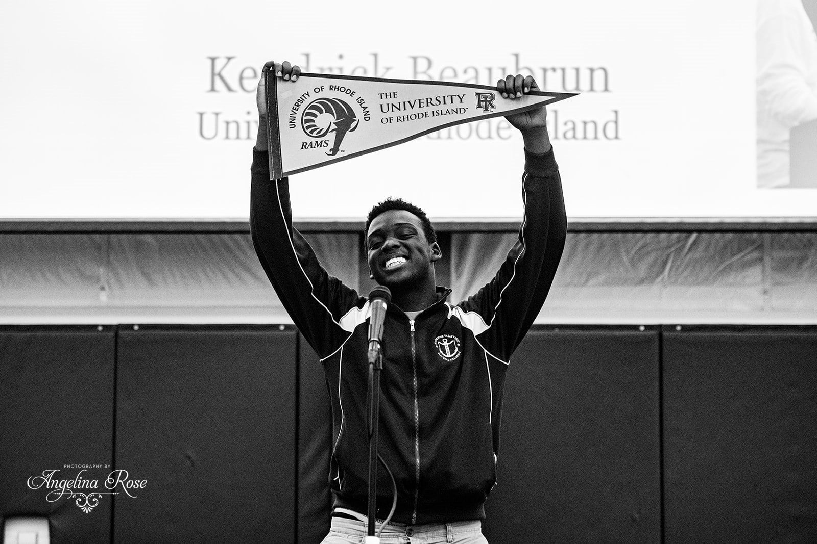 Scholar holding up URI banner