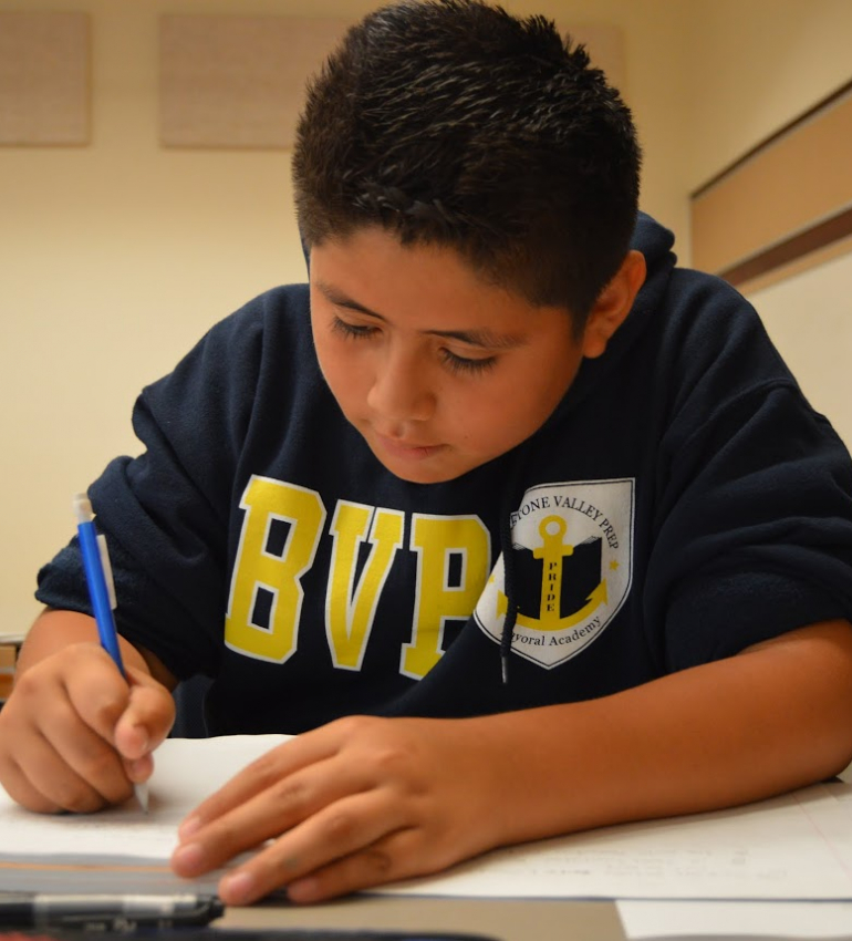 A middle school student writing in his notebook.